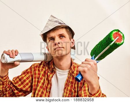 Repair home man holding paint roller for wallpaper. Tired and frustrated male in newspaper cap renovation apartment. Paint bank and roll paper background on isolated. Young Student Builder.