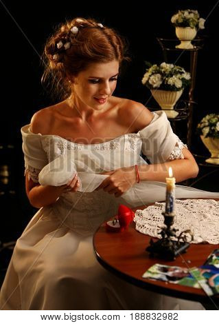 Bride thinking about choice of groom. Woman in wedding dress dreams of holiday night. Girl is preparing for ceremony. Candle stands on table decorated with lacy napkin. Black background.