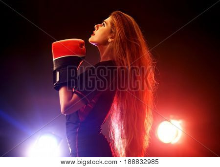Boxing women fitness exercises in gym. Sport workout on ring .Boxer wearing red gloves to box in ring. Martial arts female with backlight in the background.