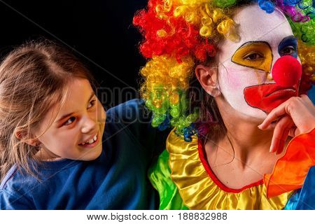Single parent family. Tired mom after work as clown on birthday on dark background. Mother angry child and girl apology. Adult kid relationship. Social problem mad parent.