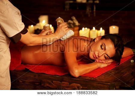 Massage of woman in spa salon. Girl on candles background in spa salon. Luxary interior in oriental therapy salon. Close up of female hands give herbs hot ball therapy. Alternative medicine.