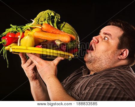 Diet fat man eating healthy food with a lot of vegetables for overweight person. Male trying to lose weight and rejoices at advent of summer and vitamins