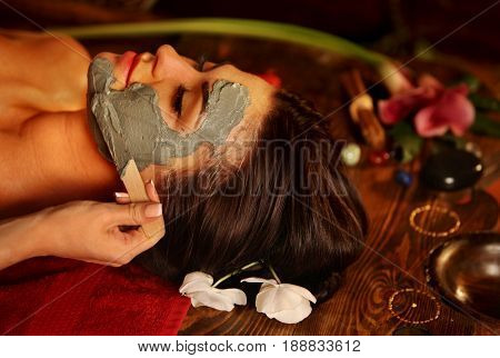 Mud facial mask of woman in spa salon. Back massage with clay full face . Girl on luxary aromatherapy interior with oriental therapy room. Crop of female with flower lying on wooden spa bed.