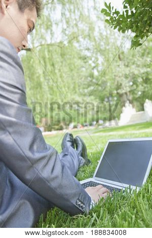Chinese businessman using laptop in park