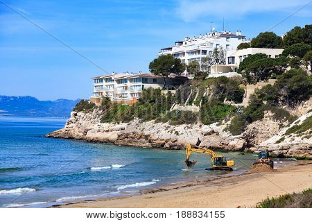 View of the empty beach with the bulldozer and the excavator. Salou, Spain