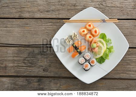 Set of assorted sushi served on tray against wooden background