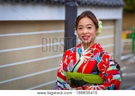 KYOTO, JAPAN - NOVEMBER 11, 2016:Young woman wearing traditional japanese kimono walk on the street of Gion, Kyoto old town, Japan. Kimono is a Japanese traditional garment.