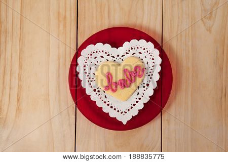 Heart shaped cookie iced with pink cream in text babe on wooden table
