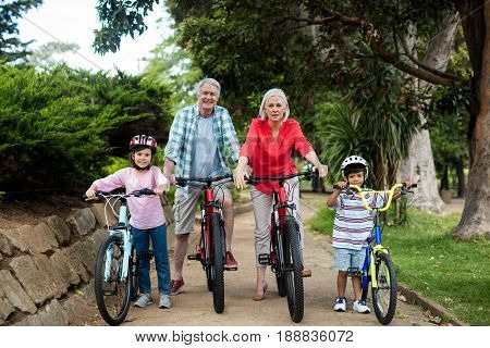 Portrait of multi-generation family standing with bicycle in park on a sunny day