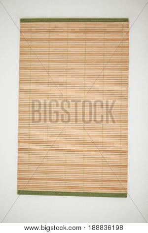 Straw sushi mat against white background