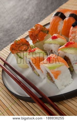 Close-up of assorted sushi set served with chopsticks on sushi mat against black background