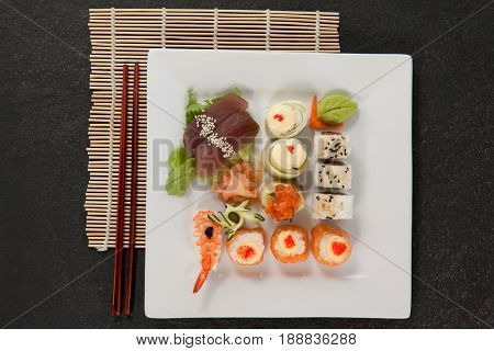 Assorted sushi set served with chopsticks in white plate on sushi mat black background