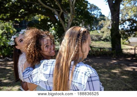 Happy female friends standing together with arm around in park