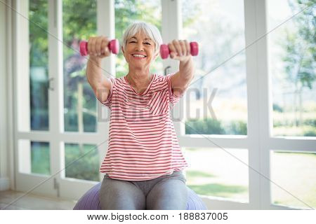 Happy senior woman exercising with dumbells at home