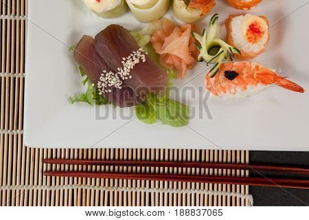 Close-up of assorted sushi set served with chopsticks in white plate on sushi mat
