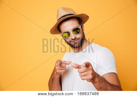 Image of handsome man in summer hat looking camera isolated and pointing.