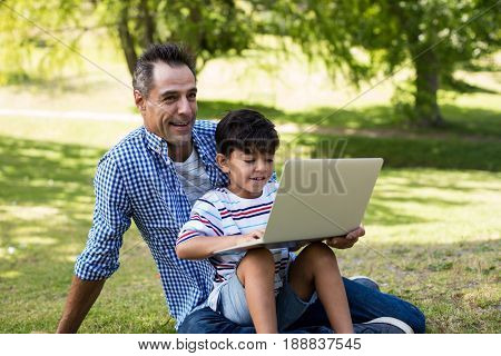 Boy sitting on his fathers lap and using laptop in park on a sunny day