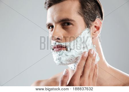Photo of young concentrated man standing isolated over grey background with shaving foam on face. Looking aside.