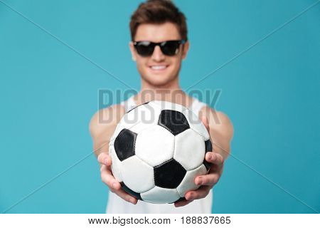 Picture of young cheerful man standing over blue isolated background holding foot ball. Looking at camera. Focus on ball.