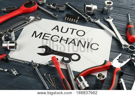 Paper with AUTO MECHANIC text and tools on wooden table