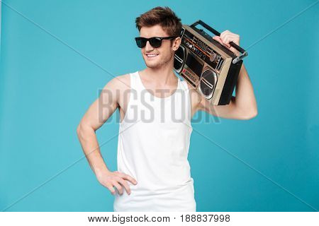 Image of young happy man standing over blue isolated background holding tape recorder. Looking aside.