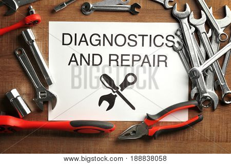 Paper with DIAGNOSTICS AND REPAIR text, tools on wooden table