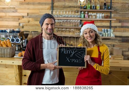 Portrait of smiling waitress and owner standing with merry x mas sign board in cafe