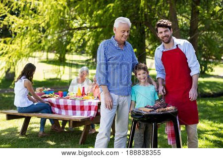 Portrait of grandfather, father and son barbequing in the park