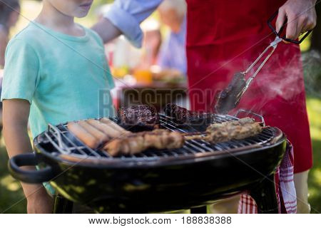 Mid section of father and son barbequing in the park during day