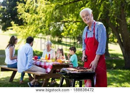Portrait of senior man barbequing with family in background