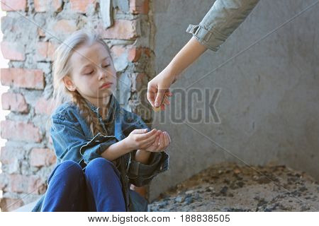 Woman giving money to poor little girl outdoors