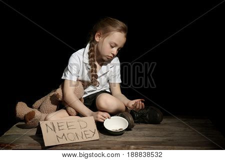 Poor little girl with bowl and piece of cardboard on black background