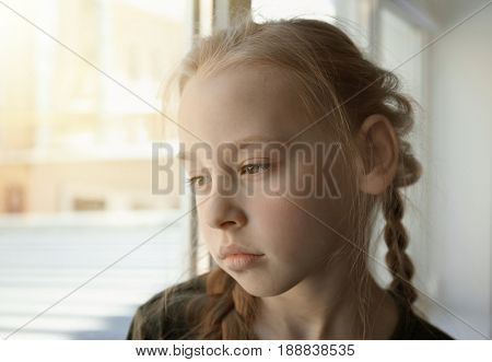 Sad little girl near window, closeup. Concept of poorness