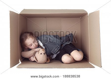 Poor little girl sleeping in cardboard box on white background