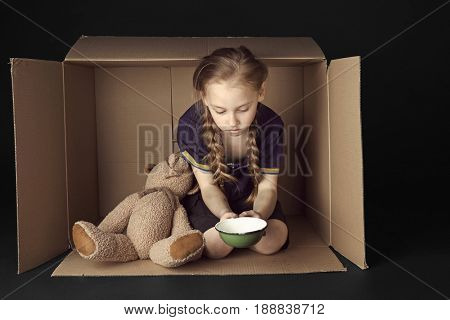 Poor little girl with empty bowl and toy bear sitting in cardboard box on black background