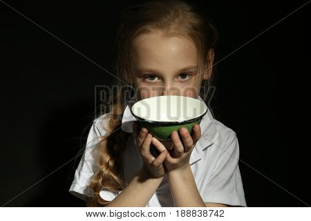 Poor little girl with empty bowl on black background