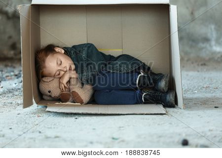 Poor little girl sleeping in cardboard box on street