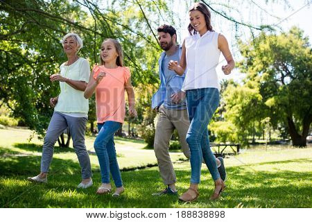 Multi generation family running in park on a sunny day