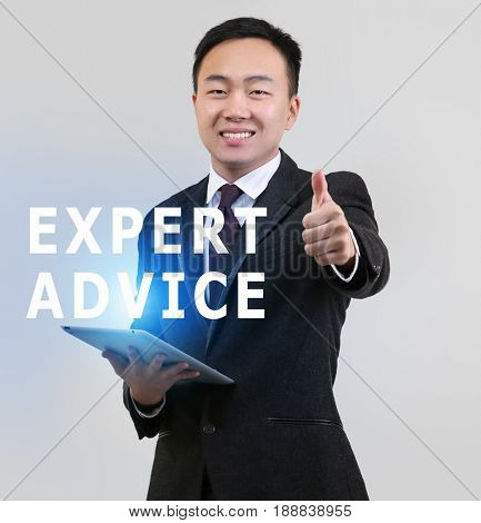 Expert advice concept. Young man with tablet on light background