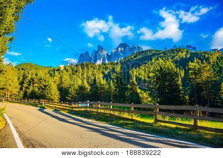 Wooden fence along the asphalt road. Summer sunset. Magnificent serrated cliffs of Dolomites, Tirol.  The concept of eco-tourism