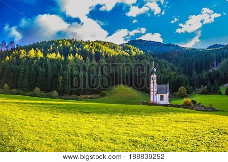 The concept of eco-tourism in Tirol. The famous church of St. Mary Magdalene and bell tower in a mountain valley. Dolomites, Tyrol, summer sunset