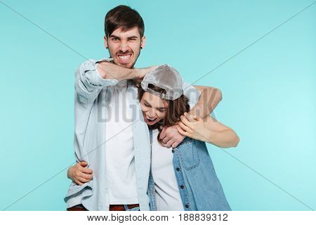Image of joyful man playing and torturing his displeased young sister isolated.
