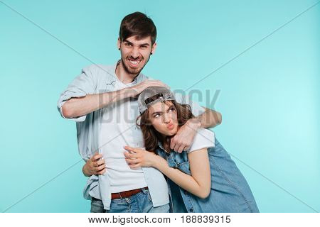 Joyful man playing and torturing his displeased young sister isolated