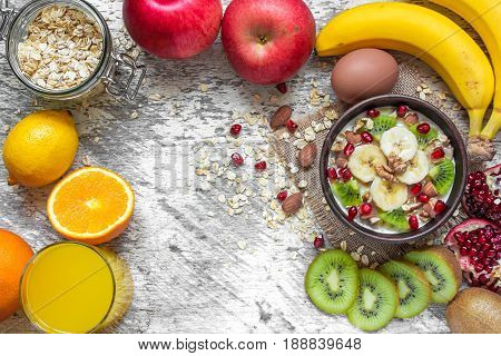 oatmeal porridge with banana kiwi fruit pomegranate cinnamon and nuts in a bowl on white wooden background with egg apple and orange juice for healthy breakfast. top view with copy space