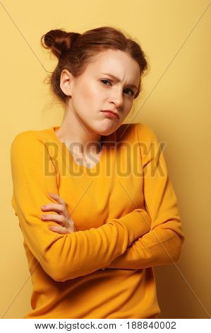frowning young woman thinking on yellow background