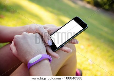 Woman with fitness band on her wrist using her mobile phone in the park