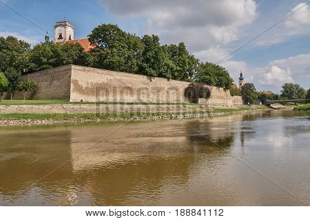 View in Gyor from the Raba river with castle wall reflecting on the water