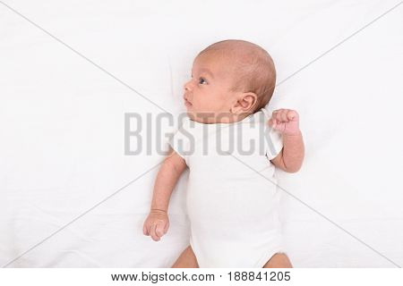 Mixed race south asian and caucasian newborn baby on white sheet