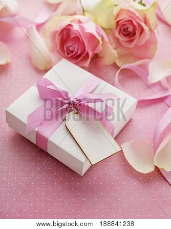 gift box tied with pink ribbon bow, rose flowers