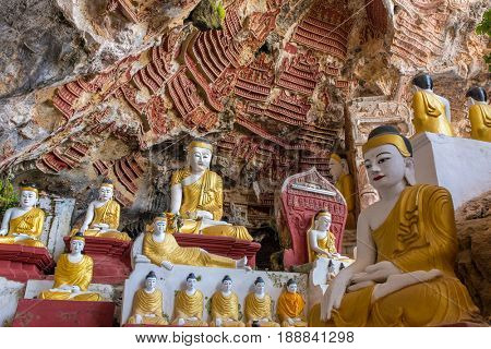Old temple with Buddhas statues and religious carving on limestone rock in sacred Kaw Goon cave near Hpa-An in Myanmar (Burma)